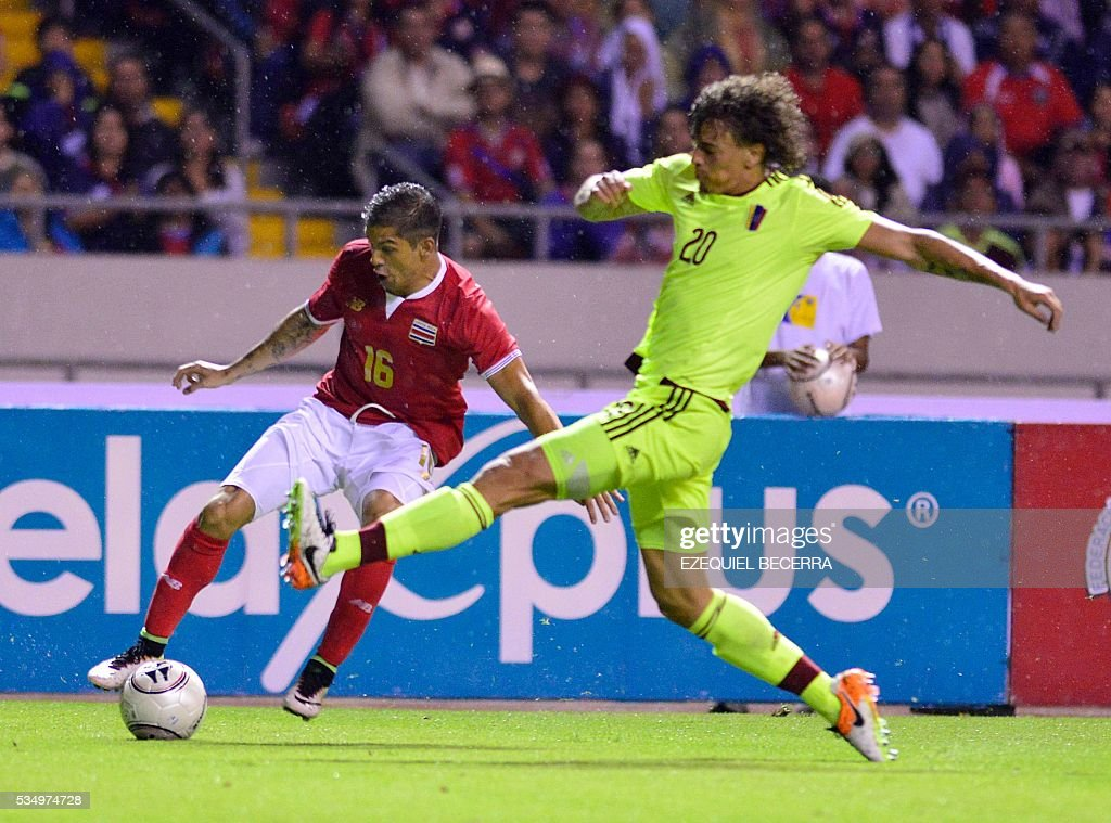 Costa Rican player Christian Gamboa (L) vies for the ball with Rolf Feltscher (R) of Venezuela during a friendly match at the National Stadium in San Jose City on May 27, 2016. / AFP / Ezequiel Becerra