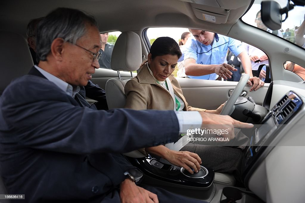 Costa Rican President Laura Chinchilla (R) and Japanese ambassador Yoshiharu Namiki drive a car powered by solar energy during the inauguration of the Miravalles Solar Power Plant in Miravalles, 220 km north of San Jose, on November 22, 2012. Costa Rica inaugurated the largest plant of electricity from solar energy in Central America, which may generate 1.2 gigawats a year and was built with funds from the Japanese government. AFP PHOTO/Rodrigo ARANGUA