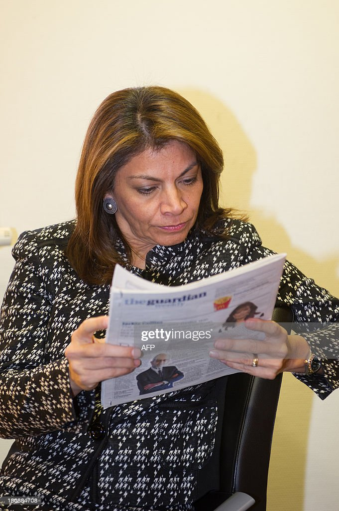 Costa Rican President Laura Chinchilla reads a newspaper on November 4, 2013 while waiting for the president of the Poitou-Charente region at the Euro-Latino American political science university campus in the central French town of Poitiers.
