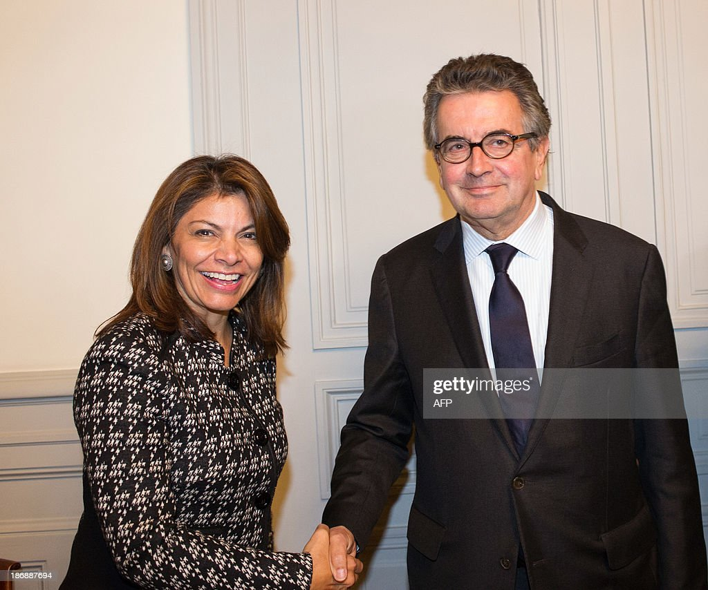 Costa Rican President Laura Chinchilla (L) shakes hands with Poitiers' mayor Alain Claeys prior to a meeting with students, on November 4, 2013 at the Euro-Latino American political science university campus in the central French town of Poitiers, as part of her official visit to France.