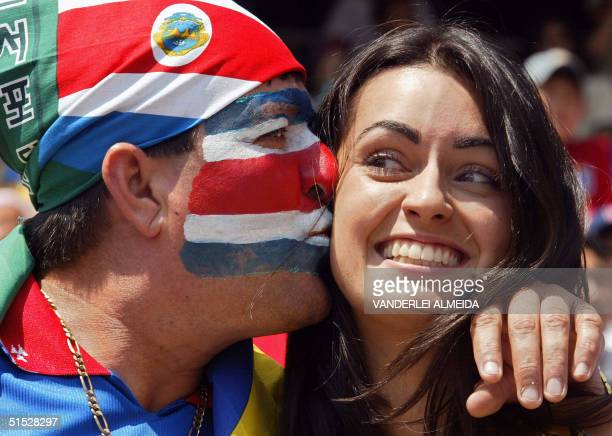 Costa Rican supporter kisses a Brazilian supporter prior to the start of their Group C match at the 2002 FIFA World Cup Korea/Japan in Suwon 13 June...