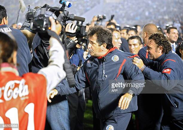 Costa Rica's coach Rene Simoes is held back by an assistant during a scuffle during their FIFA World Cup South Africa 2010 qualifier football match...