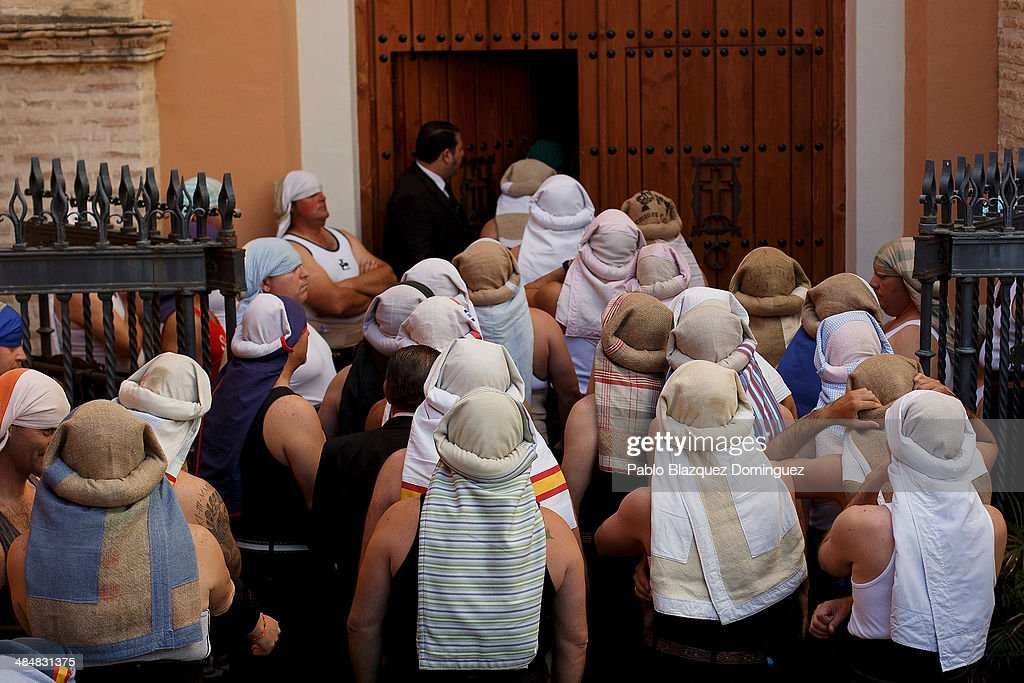 'Costaleros' from 'Vera-Cruz' brotherhood queue to enter the church to start of a procession on April 14, 2014 in Seville, Spain. Easter week is traditionally celebrated with processions in most Spanish towns.