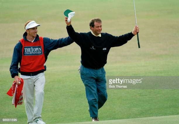 Costantino Rocca of Italy celebrates with his caddy after sinking a long putt on the 18th green to force a playoff in the British Open Golf...