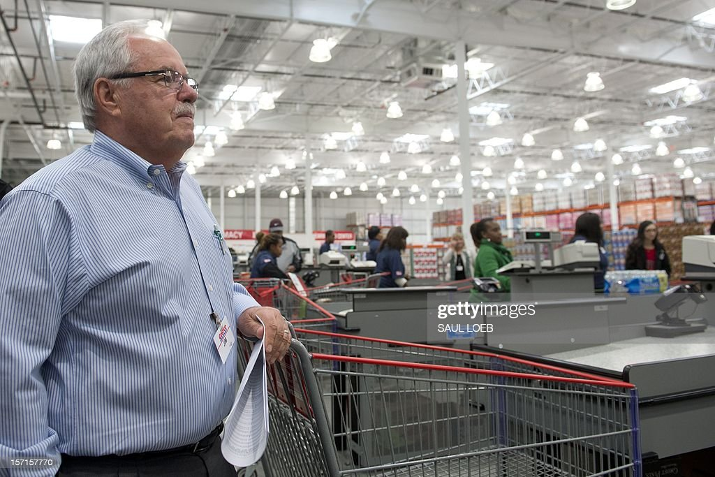 Costco co-founder Jim Sinegal walks through a Costco store while US Vice President Joe Biden makes a shopping trip in Washington, DC, on November 29, 2012. Biden made the visit to the first Costco store located in Washington, DC, during its grand opening. AFP PHOTO / Saul LOEB