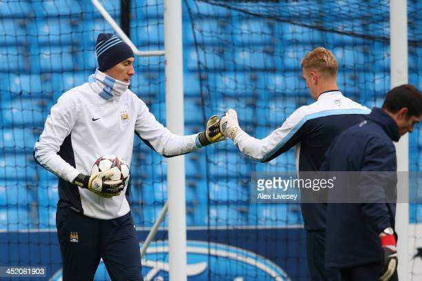 Costel Pantilimon and Joe Hart of Manchester City touch gloves during a training session at the Etihad Stadium on November 26 2013 in Manchester...