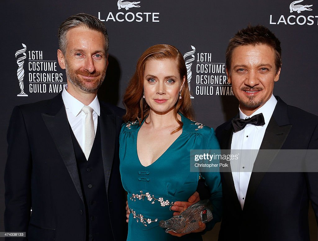 Costume designer Michael Wilkinson, honoree <a gi-track='captionPersonalityLinkClicked' href=/galleries/search?phrase=Amy+Adams&family=editorial&specificpeople=213938 ng-click='$event.stopPropagation()'>Amy Adams</a> and actor <a gi-track='captionPersonalityLinkClicked' href=/galleries/search?phrase=Jeremy+Renner&family=editorial&specificpeople=708701 ng-click='$event.stopPropagation()'>Jeremy Renner</a> pose with the Lacoste Spotlight Award during the 16th Costume Designers Guild Awards with presenting sponsor Lacoste at The Beverly Hilton Hotel on February 22, 2014 in Beverly Hills, California.