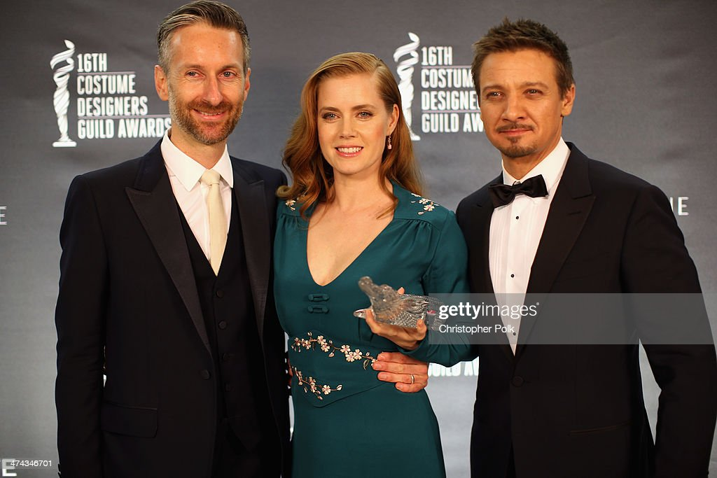 Costume designer Michael Wilkinson, LACOSTE Spotlight Award Honoree Amy Adams, and actor Jeremy Renner attend the 16th Costume Designers Guild Awards with presenting sponsor Lacoste at The Beverly Hilton Hotel on February 22, 2014 in Beverly Hills, California.