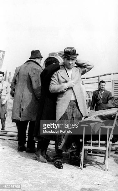 A costume maker putting Italian actor Paolo Stoppa's jacket right on the set of Miracle in Milan Milan 1951