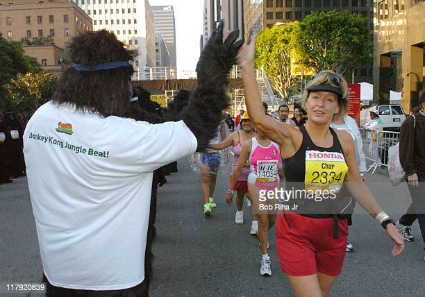 Costumed apes give highfives to marathon runners prior to the start of the 20th running of the LA Marathon Sunday March 6 2005 in Los Angeles...