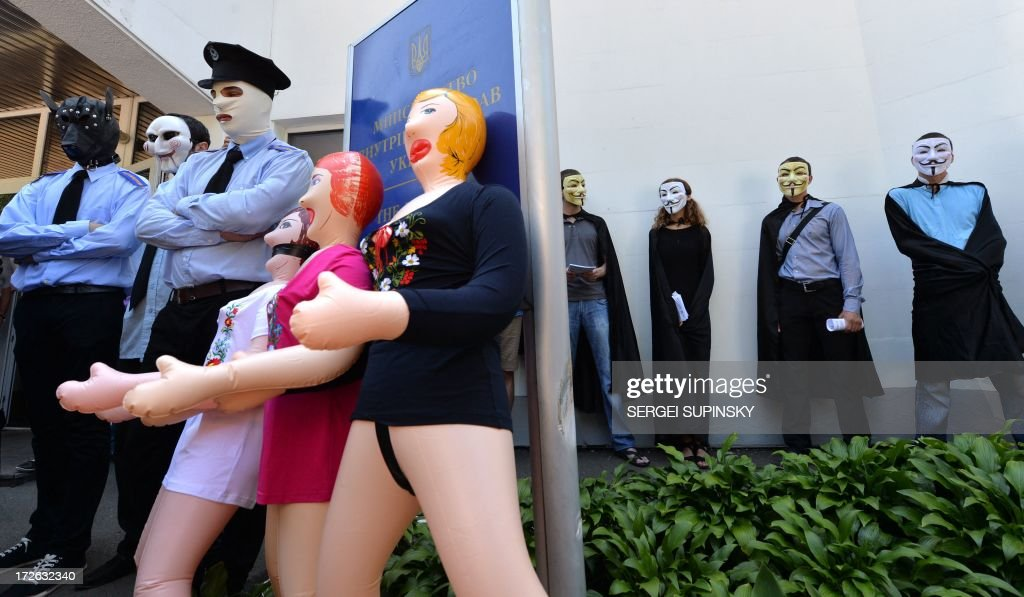 Costumed as policemen, activists of the public initiative 'The movement of Guy Fawkes' brought dolls for adults gifting them to the Ukrainian Interior Ministry officials during a protest-performance against the police outrage in front of the ministry in Kiev on July 4, 2013. At this time some activists conduct a rally to support the residents of the small Ukrainian ciry of Vradiyivka, Mykolayiv region, who stormed the local police headquarters, after two police officers brutally beated and raped 29-year-old Iryna Krashkova. The huge outrage prompted Ukraine's President Viktor Yanukovych to order a top-level enquiry into the gang rape of Krashkova.