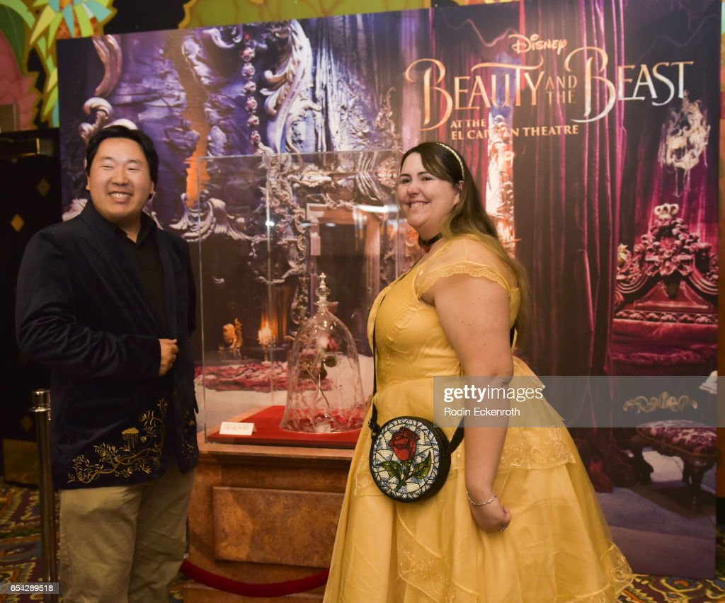 Costumed attendees pose for portait in front of magical rose movie prop at opening night of Disney's 'Beauty And The Beast' at El Capitan Theatre on March 16, 2017 in Los Angeles, California.