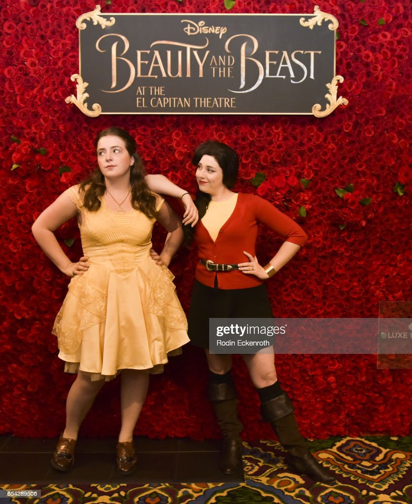 Costumed attendees pose for portrait in front of rose wall at the opening night of Disney's 'Beauty And The Beast' at El Capitan Theatre on March 16, 2017 in Los Angeles, California.
