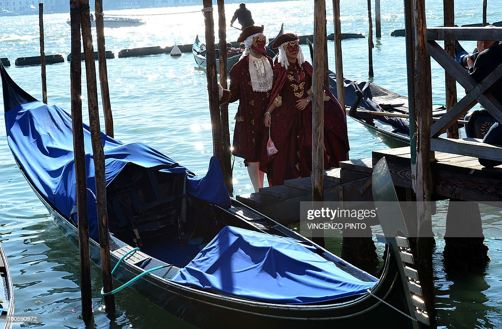 A costumed couple poses near gondolas during the carnival on February 3, 2013 in Venice. The 2013 edition of the Venice carnival is untitled ' Live in Colour' and runs from January 26 to February 12.