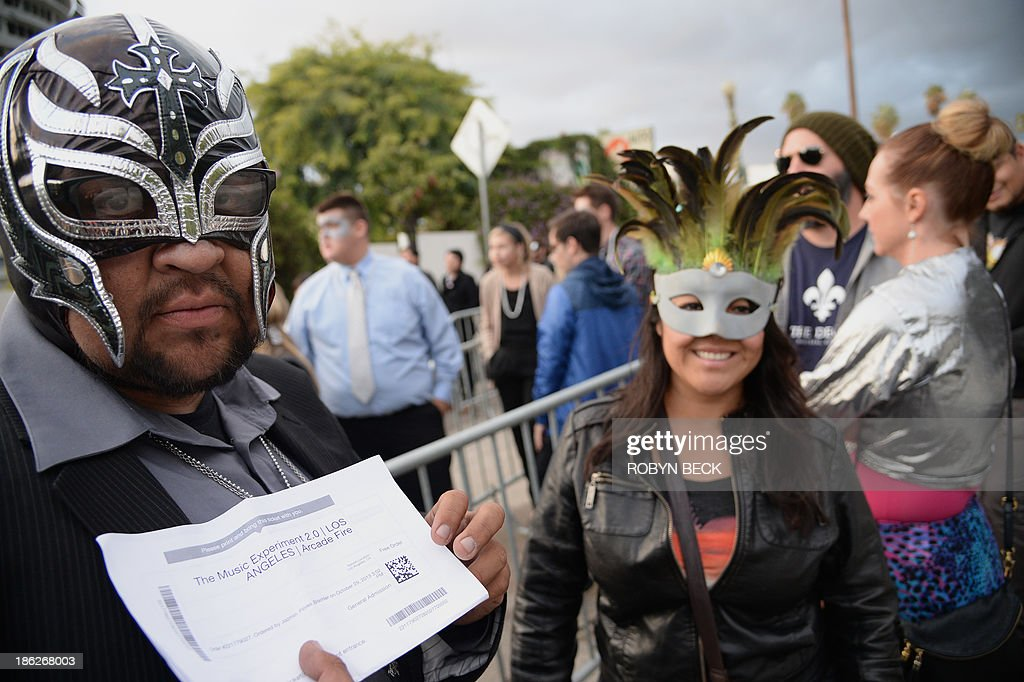 A costumed fan named Cisco Rocks shows his ticket for an impromptu concert by the indie rock band Arcade Fire, outside the iconic Capitol Records building in Hollywood, California October 29, 2013. Arcade Fire staged the event to mark the release of their new album Reflektor.' No tickets were for sale to the show - fans secured entry only through web-based 'social media challenges' and were asked to wear constumes to the concert.