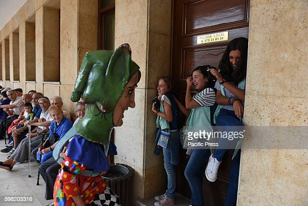 A costumed figure 'Cabezudo' chases a several girls during the 'La Bajada de Jesús' festival in Almazán north of Spain