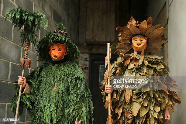 Costumed participants wait for the start of the celebrations of 'La Vijanera' carnival in Silio in the northern Spanish province of Cantabria on...