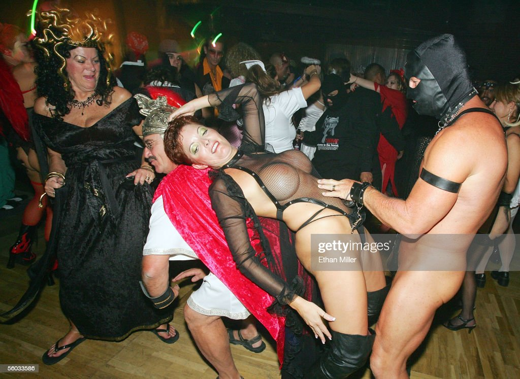 Costumed revelers including Traci (2nd-R) and Roy (R) (no last names given) of Nevada dance at the 10th annual Fetish & Fantasy Halloween Ball at the Las Vegas Sports Center on October 29, 2005 in Las Vegas, Nevada.