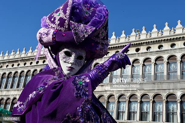 A costumed reveller poses at St Mark's square during the carnival on February 3 2013 in Venice The 2013 edition of the Venice carnival is untitled '...