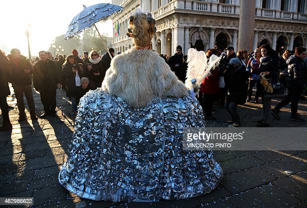 A costumed reveller poses at St Mark's square during the Venice Carnival on February 8 2015 in Venice The 2015 edition of the Venice carnival is...