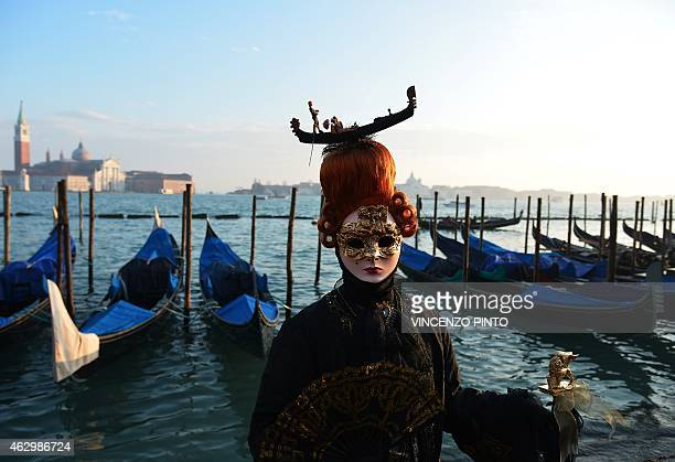A costumed reveller poses in front of gondolas at St Mark's square during the Venice Carnival on February 8 2015 in Venice The 2015 edition of the...