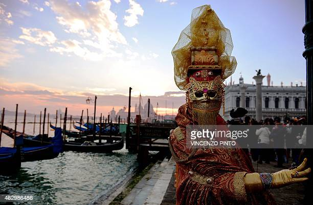 A costumed reveller poses in front of gondolas during the Venice Carnival on February 8 2015 in Venice The 2015 edition of the Venice carnival is...