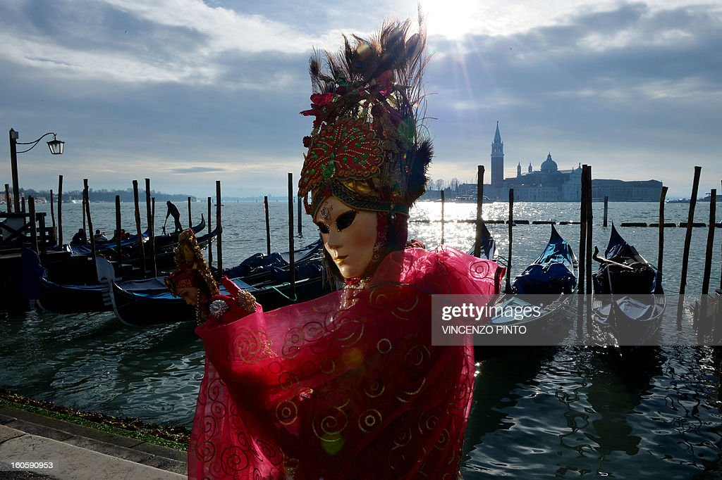 A costumed reveller poses near gondolas during the carnival on February 3, 2013 in Venice. The 2013 edition of the Venice carnival is untitled ' Live in Colour' and runs from January 26 to February 12. AFP PHOTO / VINCENZO PINTO