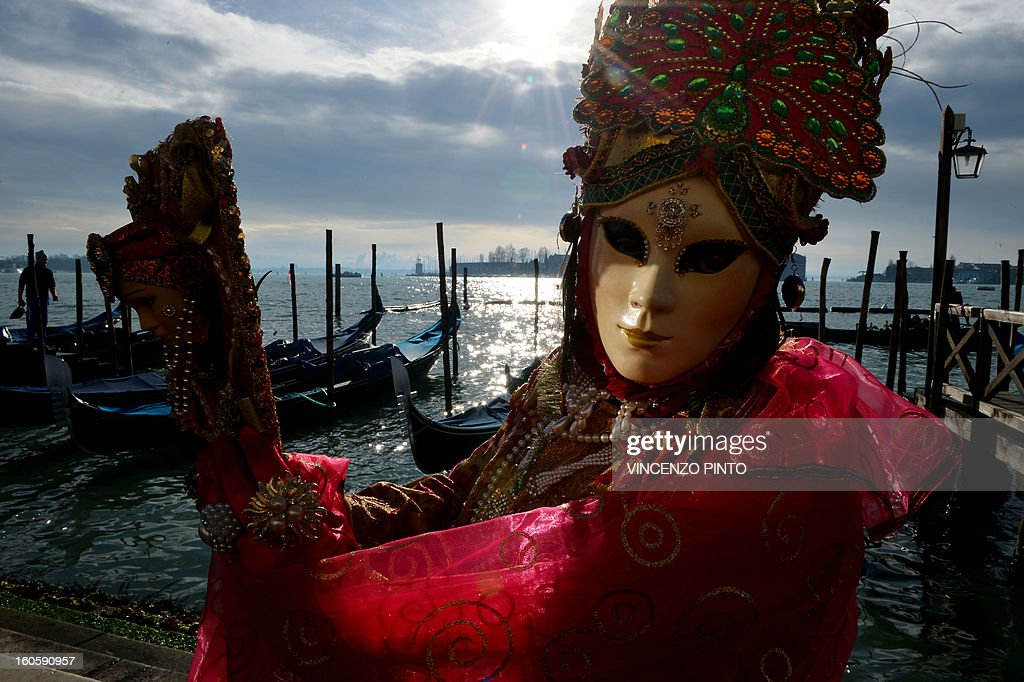 A costumed reveller poses near gondolas during the carnival on February 3, 2013 in Venice. The 2013 edition of the Venice carnival is untitled ' Live in Colour' and runs from January 26 to February 12.