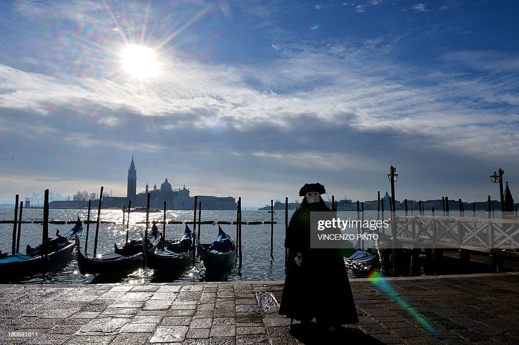 A costumed reveller poses near St Mark's square during the carnival on February 3, 2013 in Venice. The 2013 edition of the Venice carnival is untitled ' Live in Colour' and runs from January 26 to February 12. AFP PHOTO / VINCENZO PINTO