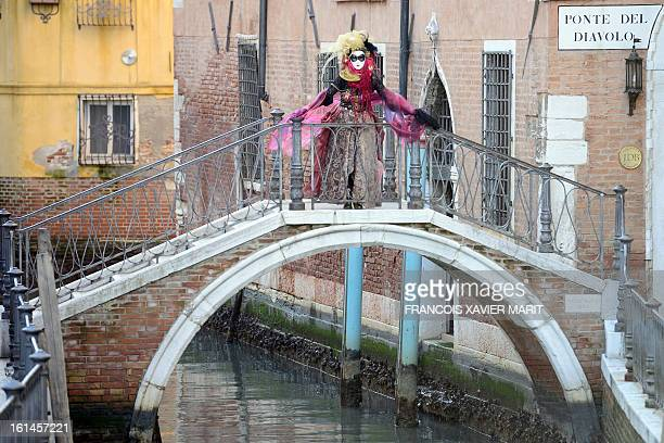 A costumed reveller stands on the 'devil's bridge' during the carnival on February 8 2013 in Venice The 2013 edition of the Venice carnival is...