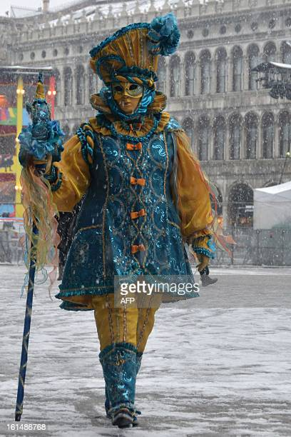 A costumed reveller walks on St Mark's square covered with snow during the carnival on February 11 2013 in Venice The 2013 edition of the Venice...