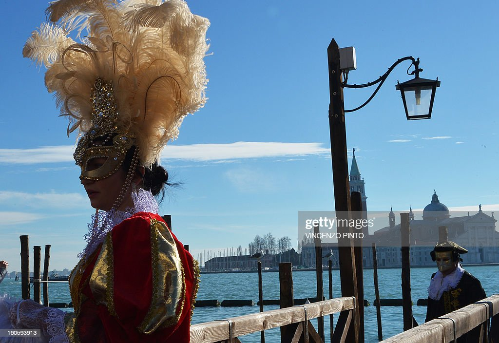 Costumed revellers arrive at St Mark's square during the carnival on February 3, 2013 in Venice. The 2013 edition of the Venice carnival is untitled ' Live in Colour' and runs from January 26 to February 12. AFP PHOTO / VINCENZO PINTO