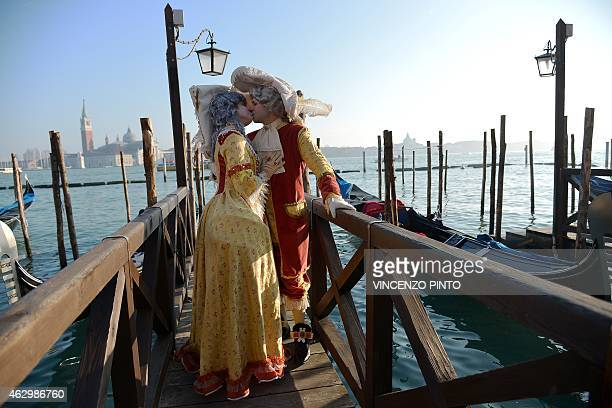 Costumed revellers kiss in front of gondolas at St Mark's square during the Venice Carnival on February 8 2015 in Venice The 2015 edition of the...