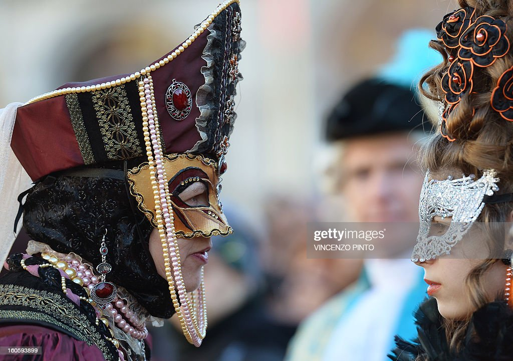 Costumed revellers pose at St Mark's square during the carnival on February 3, 2013 in Venice. The 2013 edition of the Venice carnival is untitled ' Live in Colour' and runs from January 26 to February 12. AFP PHOTO / VINCENZO PINTO