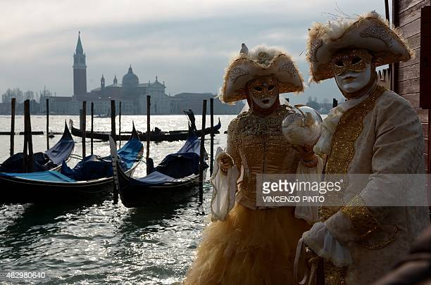 Costumed revellers pose at St Mark's square during the Venice Carnival on February 8 2015 in Venice The 2015 edition of the Venice carnival is...