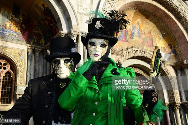 Costumed revellers pose in front of St Mark's basilica at St mark's square during the carnival on February 7 2013 in Venice The 2013 edition of the...