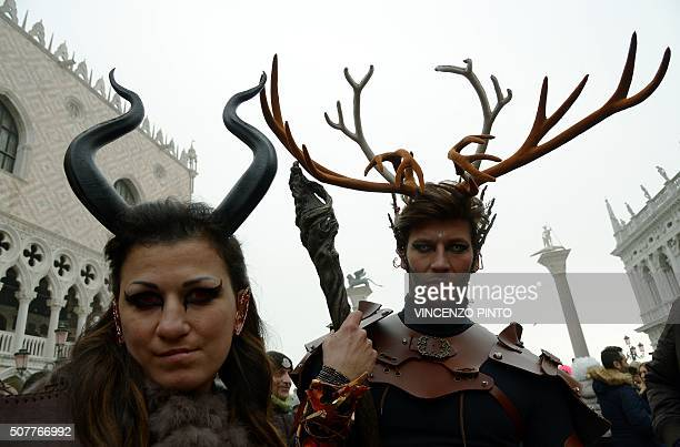 Costumed revellers pose in St Mark's square after the officially launch of the Venice Carnival on January 31 2016 in Venice The 2016 edition of the...