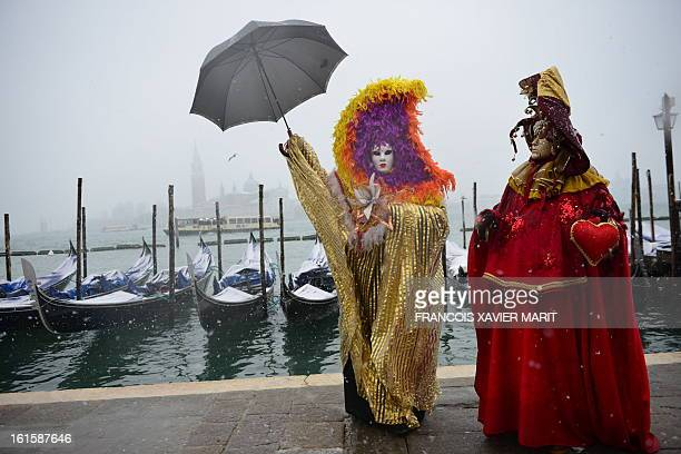Costumed revellers pose near St Mark's square covered with snow during the carnival on February 11 2013 in Venice The 2013 edition of the Venice...