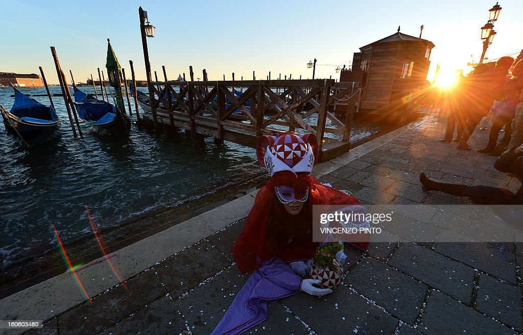 Costumed revellers pose near St Mark's square during the carnival on February 3, 2013 in Venice. The 2013 edition of the Venice carnival is untitled ' Live in Colour' and runs from January 26 to February 12. AFP PHOTO / VINCENZO PINTO