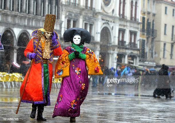 Costumed revellers walk on St Mark's square covered with snow during the carnival on February 11 2013 in Venice The 2013 edition of the Venice...
