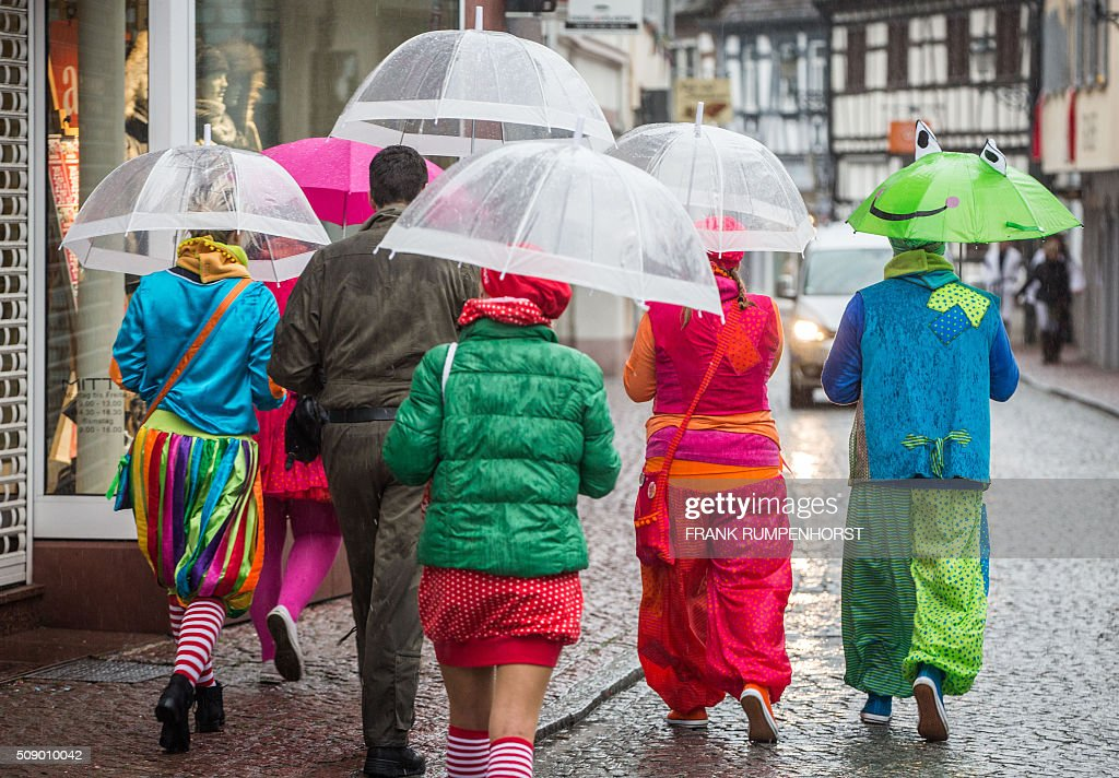 Costumed revellers walk through the streets of Seligenstadt, western Germany, after the city's traditional carnival street parade was cancelled, on Rose Monday (Rosenmontag), February 8, 2016. / AFP / dpa / Frank Rumpenhorst / Germany OUT