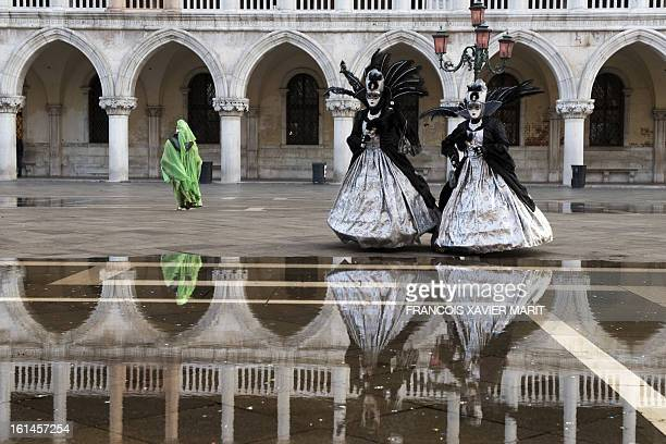 Costumed revellers walks on St mark's square during the carnival on February 8 2013 in Venice The 2013 edition of the Venice carnival is untitled '...