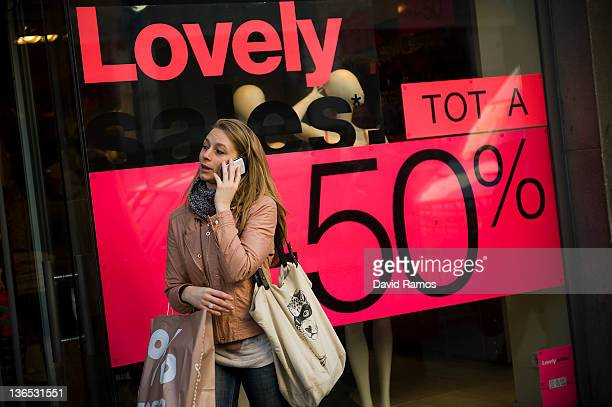 A costumer talks on a mobile phone past a display window of a store advertising sales on the first day of the winter sales in Spain on January 7 2012...