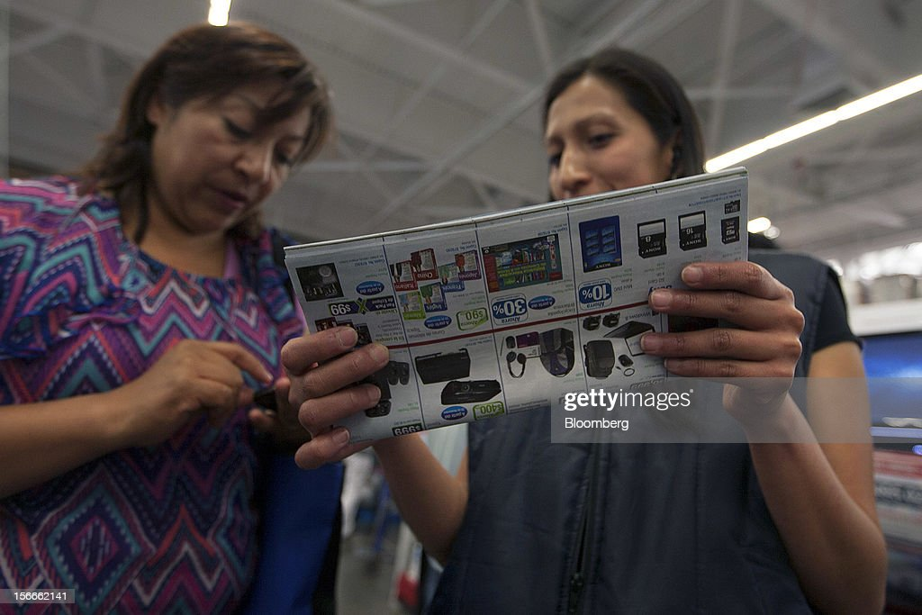 Costumers look for discount offers in the electronics department inside a Sam's Club store in Mexico City, Mexico on Saturday, Nov. 17, 2012. El Buen Fin, Mexico's equivalent of Black Friday, when the year's biggest discounts are offered by participating stores, is held on the third weekend of November and will run through Nov. 19. Photographer: Susana Gonzalez/Bloomberg via Getty Images