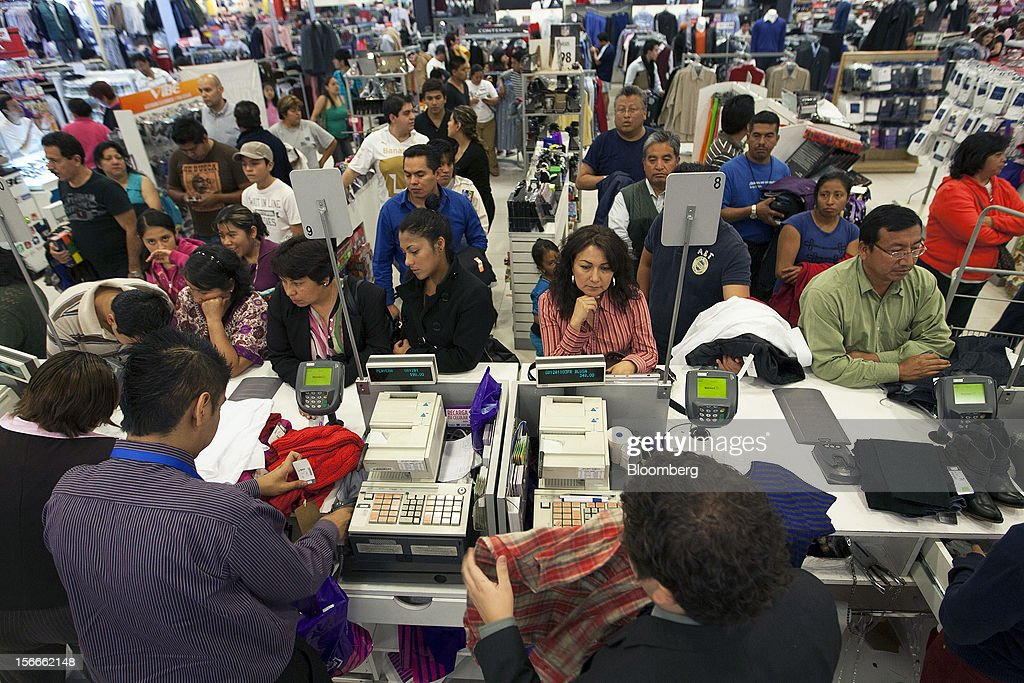 Costumers wait in line to pay for their merchandise inside Wal-Mart de Mexico SAB de CV's Suburbia store in Mexico City, Mexico on Saturday, Nov. 17, 2012. El Buen Fin, Mexico's equivalent of Black Friday, when the year's biggest discounts are offered by participating stores, is held on the third weekend of November and will run through Nov. 19. Photographer: Susana Gonzalez/Bloomberg via Getty Images