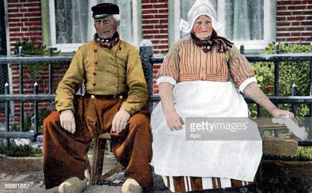 Costumes of Netherlands couple seated on a bench postcard