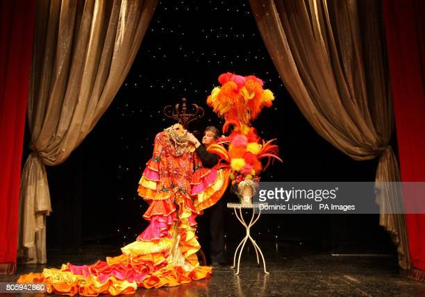 Costumier Annie Galbraith adjusts a 'Carmen Miranda' dress worn by female impersonator Danny La Rue part of a collection of his 90 costumes and gowns...