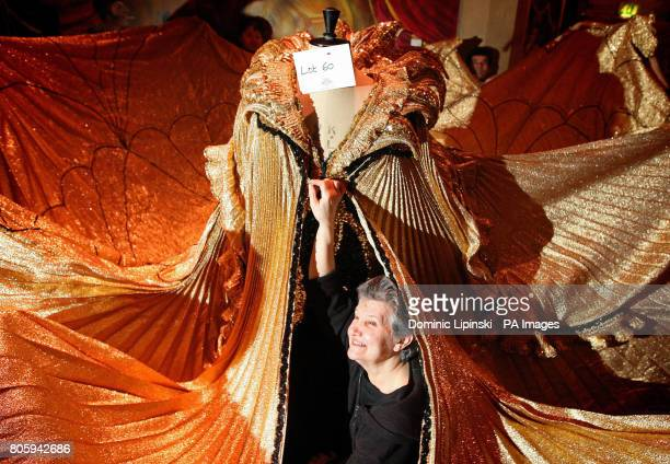 Costumier Annie Galbraith adjusts a dress worn by female impersonator Danny La Rue in his 'A Night at the Oscars' show part of a collection of his 90...