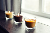 Cosy candles on an wooden table in home interior closeup