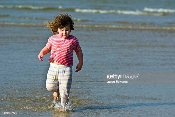 A toddler splashes through the shallows late on a summers afternoon.